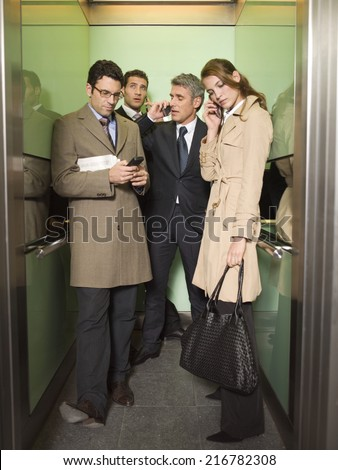 people in elevator. four business people talking on the phone. in elevator o