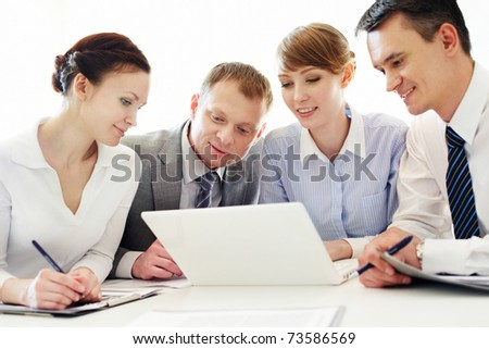 Four business people working with laptop in office