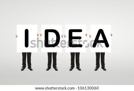 """four  businessman holding a white board with """"idea"""" symbol - stock photo"""