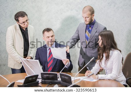 four businessmen are happily discussing in the office documents