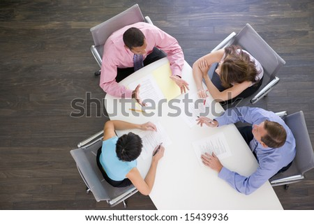Four businesspeople at boardroom table - stock photo