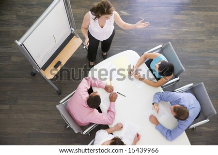 Four businesspeople at boardroom table watching presentation - stock photo