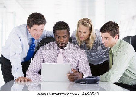 Four businesspeople in a boardroom looking at laptop - stock photo
