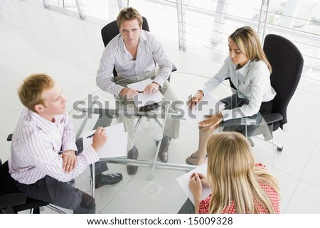 Four businesspeople in boardroom with paperwork - stock photo