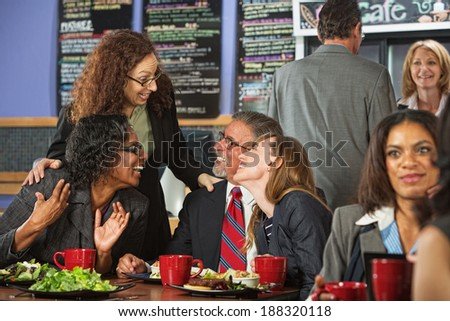 Four businesspeople laughing together during lunch in cafe - stock photo