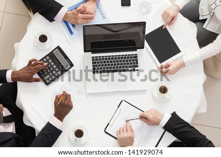 Four businesspeople on a meeting. Close-up. Top View