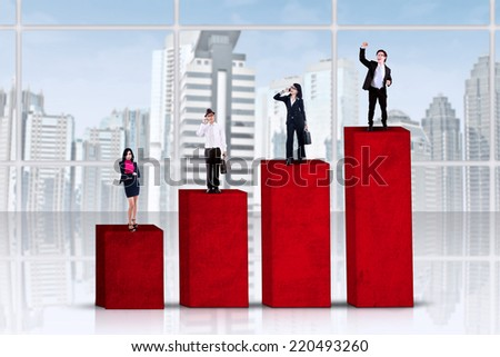 Four businesspeople standing on business chart, symbolizing business grade - stock photo