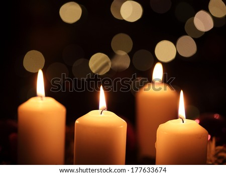 Four candles against abstract background