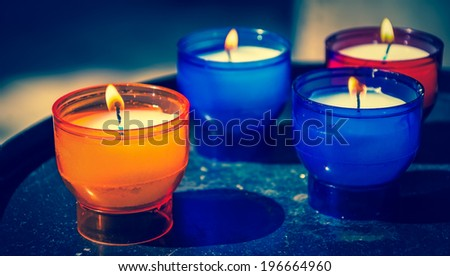 Four candles in colorful glass candlesticks in church. Religious background. Closeup. Selective focus on the foreground. Aged photo. - stock photo