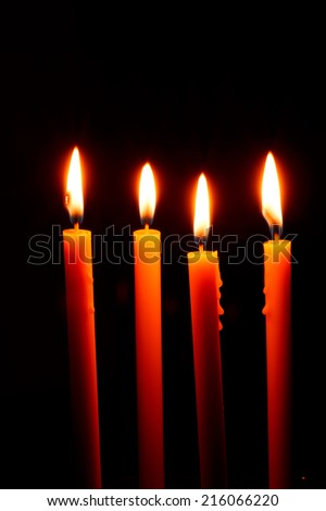 four candles on black background