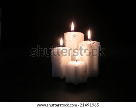 four candles with warm and magic light in black background