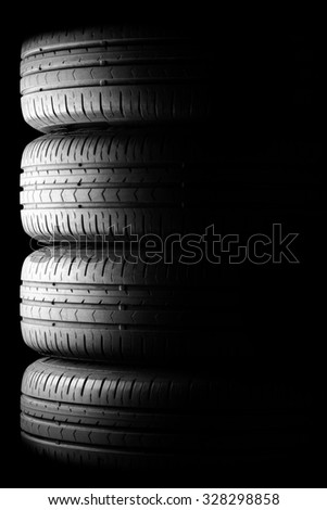 Four car summer tires in dramatic lighting - stock photo