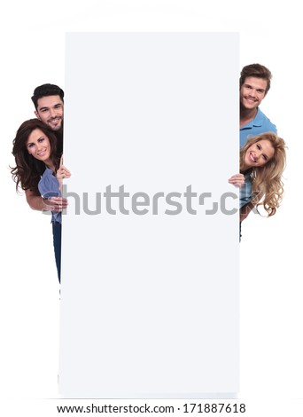 four casual happy people hiding behind a big blank billboard on white background - stock photo