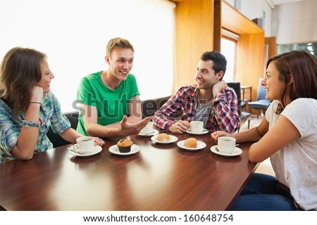 Four casual students having a cup of coffee chatting in college canteen - stock photo