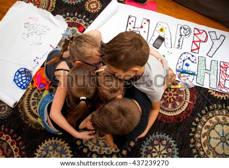 Four Caucasian Children Hug a Baby Boy on the floor of their Home