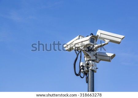 Four CCTV surveillance cameras on a pole - stock photo