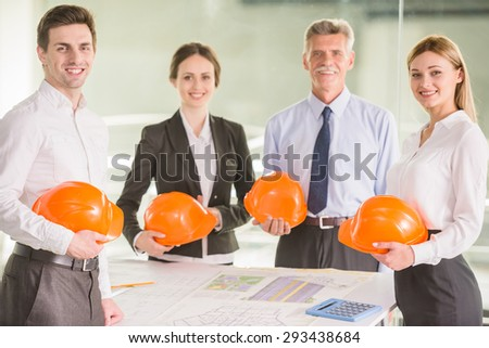 Four charismatic architects looking at plans together around a table. - stock photo