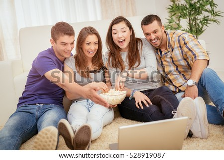 Four cheerful best friends having nice time in an apartment. They are watching movie together.