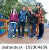 Four cheerful friend skateboarders in the skatepark - stock photo