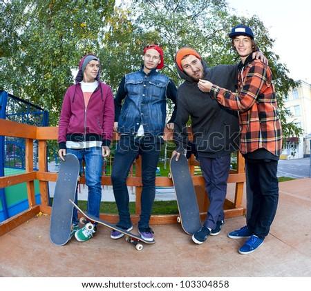 Four cheerful friend skateboarders in the skatepark - stock photo