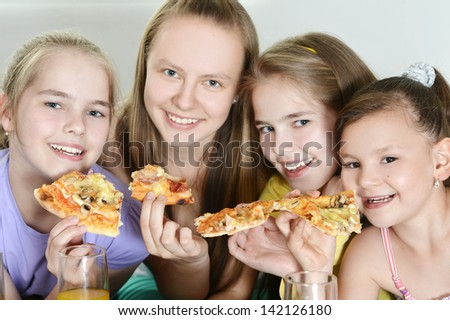 Four cheerful girls watching television together