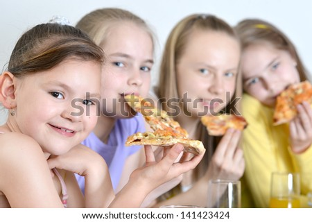 Four cheerful girls watching television together at home