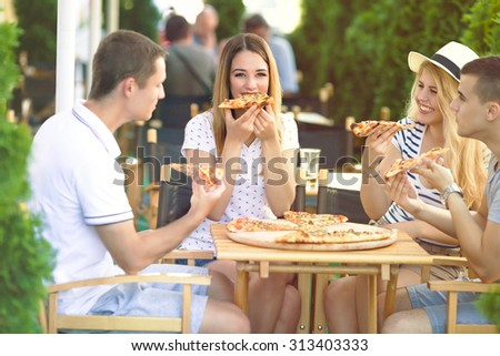 Four cheerful young friends sharing pizza in a outdoor cafe