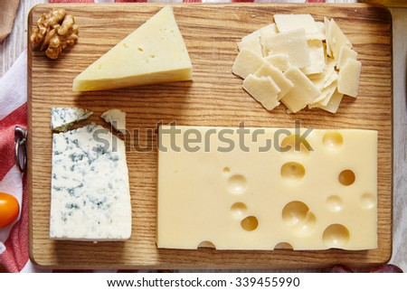 four cheeses closeup on wooden board - stock photo