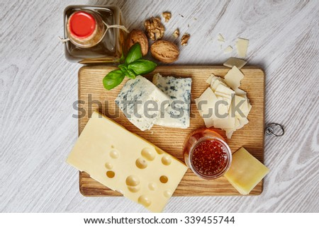 four cheeses with supplements on chopping board an white wooden  - stock photo