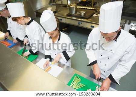 Four chefs preparing food at counter standing in a row in a kitchen