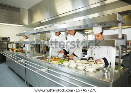 Four chefs working in a big kitchen at service time - stock photo