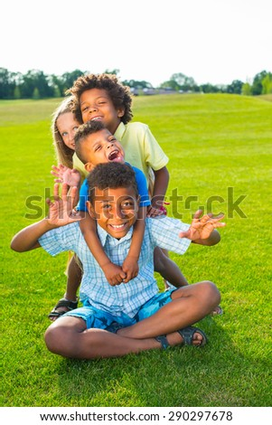 Four children are playing on the glade. They are laughing and having fun.