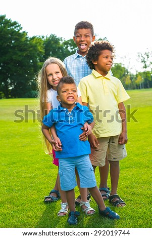 Four children are standing on the glade. They are they joking and having fun.