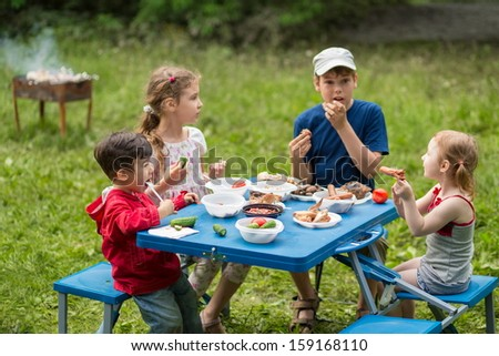 Four children eat meat with vegetables at the picnic on pembroke table, boy on the left in focus - stock photo