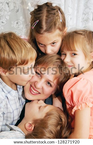 Four children kissing mother. Family concept, happiness and love. - stock photo