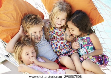 Four Children Relaxing In Garden Hammock Together - stock photo