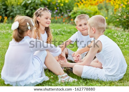 Four children sit on grass at lawn holding hands, one boy yalks, other listen and look at him - stock photo