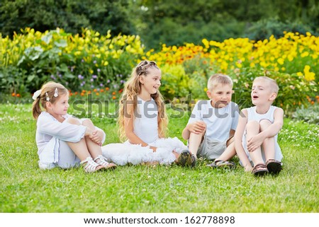 Four children sit on grass at lawn, one boy sings with eyes closed, other listen and look at him  - stock photo