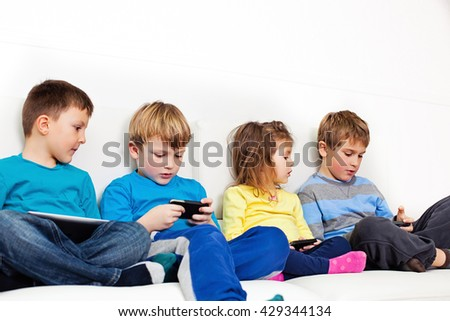 Four children sitting on a couch using smartphones and a digital tablet. - stock photo