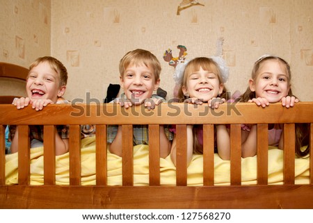 Four children, two brothers and two sisters lying on the bed, looking over a side and laughing. Happy family. Triplet and their older sister. - stock photo