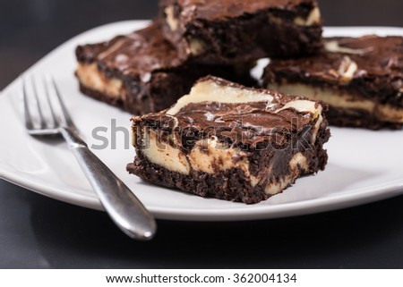 Four chocolate cheesecake swirl brownies and a fork on a white plate. - stock photo