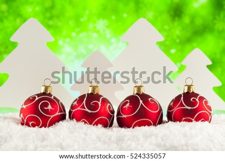 Four Christmas baubles on green abstract background