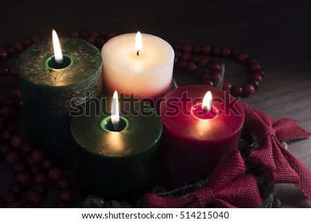 Four Christmas candles with red bows.