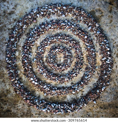 Four circles of small pebbles on the stone - stock photo