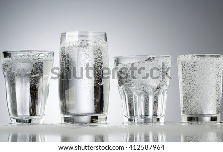 Four classic glasses with water and water bubbles - stock photo