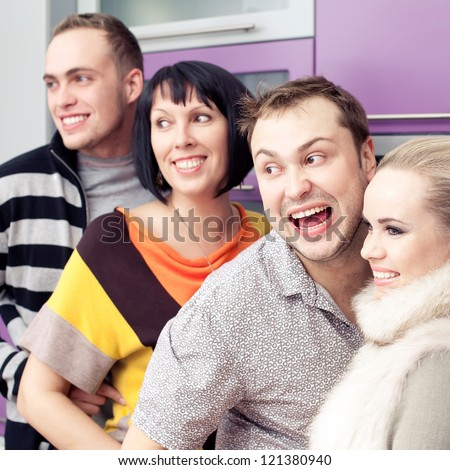 Four close friends enjoying a social gathering together and happy to see something or somebody else at home (kitchen room). Indoor shot. - stock photo