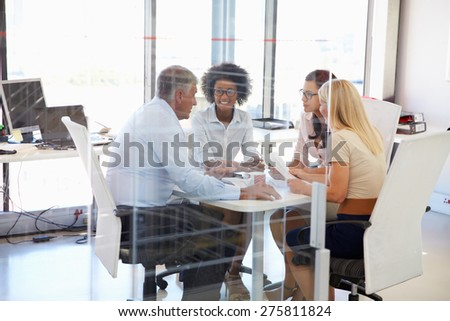 Four colleagues meeting around a table in an office - stock photo