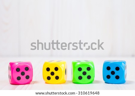 Four color dice on the white wooden background - stock photo