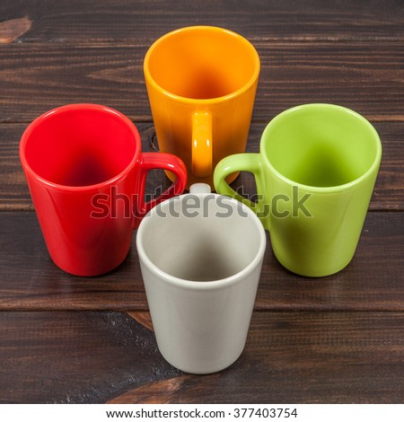 Four color empty tea cups arranged in a cross, top view - stock photo