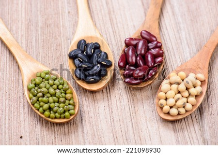 four colored beans in wooden spoon - stock photo